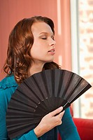 Young woman using fan
