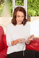 Young woman using iPhone, holding credit card