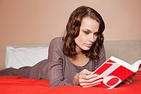 Young woman reading a book in bed (thumbnail)