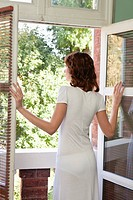Young woman opening window, rear view