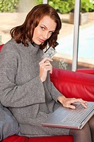 Young woman holding credit card, using laptop