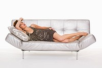 Young woman in formalwear sleeping on sofa