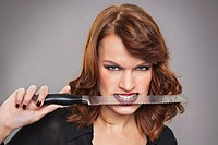 Young woman with knife between teeth (thumbnail)
