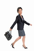 Businesswoman walking and swinging a handbag