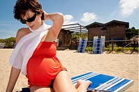 Pregnant woman sitting down on the beach by the sea