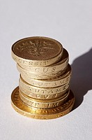 Pile of 7 English one pound coins, with one two pond coin