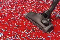 Hoovering coloured confetti spread over a red carpet, concept image of removing dust, cleaning, suppressing pollution and allergy