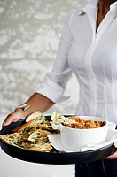 A woman holding a tray of pita chips and a cheese dip
