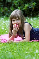 Little girl lying on a blanket eating an apple