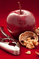 A red apple with walnuts and a nutcracker