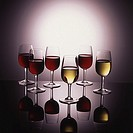 Display of wine in glasses on glowing background with reflections