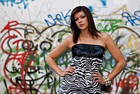 Young woman with dark hair wearing a top with a zebra pattern and posing in front of a wall with graffiti
