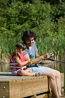 Father and daughter fishing from jetty