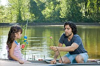 Father and daughter on rowboat with fishing rods