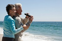Mature couple at the beach with binoculars