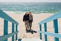 Couple walking on beach towards walkway