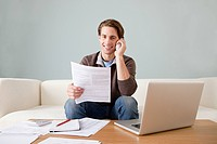 Young man with paperwork using laptop