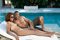 Couple lying on sun lounger by pool