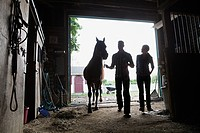 Two people with horse in stable