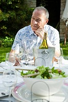 Senior man having lunch with wine outdoors