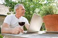 Senior man using laptop with red wine