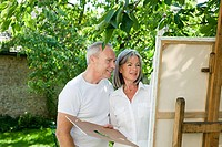 Mature couple, woman painting at easel