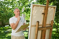 Senior man painting at easel