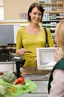 Woman at supermarket checkout
