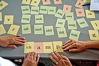 Using 'word card' components to form a complete word, a volunteer adult literacy teacher instructs an elderly Hispanic student who cannot read or writ...