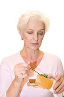 A woman putting parsley on a sausage in a baguette