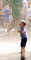 A young boy runs under the curtain of water as the after comes down full force  Children and adults were enjoying the last weeks of summer in Millenni...