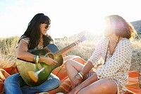 Women playing the guitar in the grass