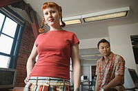 Asian man and Caucasian woman, 20s, at desk in a loft_style office.