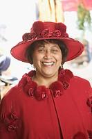 Portrait of a senior woman wearing a fancy red hat.