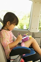 Young Asian girl in car seat with electronic toy