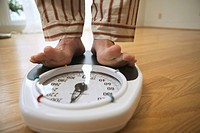 Man weighing himself on a bathroom scale