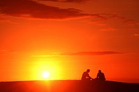 Hawaii, Oahu, Two silhouetted men enjoying the sunset.