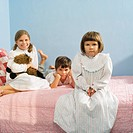 Children sitting on bed in pajamas