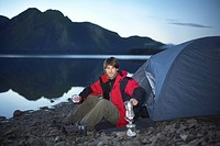 Man camping in mountains on lake