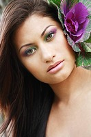 Hawaii, Oahu, Fashion model poses with plant behind ear.