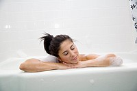 Woman resting on edge of bathtub