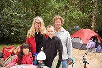 Family smiling at campsite