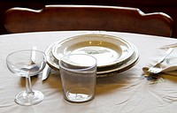 Table set with plates, cups, glasses, cover, tablecloth, spoons, forks and knives