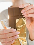 USA, New Jersey, Jersey City, Close_up of woman holding chocolate bar
