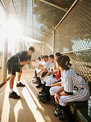USA, California, Ladera Ranch, Boys 10_11 from little league sitting on dugout while coach talking