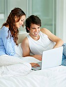 South Africa, Young couple using laptop while sitting on bed