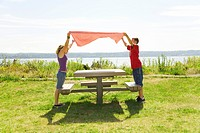Boy and girl placing table cloth on picnic table