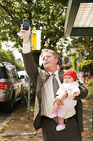 Businessman holding baby at bus stop