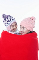mother and daughter is covering with the red blanket
