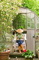 Woman sitting in backyard greenhouse